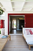 Summery wooden veranda with comfortable, upholstered lounger and bench in front of open, slatted door