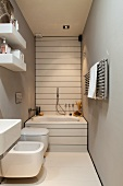 Well-appointed, narrow bathroom with grey walls
