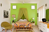 Bedroom with green mosquito net over double bed against green wall and flanked by green shell chair and white sideboard