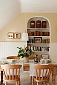 Wooden dining table with lath back dining chairs in room an alcove bookshelf