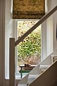 Blick von der Treppe in ein kleines Alkoven mit gemustertem Stoffrollo am Fenster