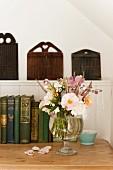 Prachtvoller Sommerstrauss in einer Glasvase vor antiken Büchern auf einer Holzkommode stehend