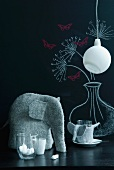 Felt elephant, glasses and minimalist pendant lamp in front of blackboard with floral drawing