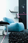 Contemporary seating area with blue upholstered armchair and leather rag rug in front of minimalist shelves and strip of blackboard on wall