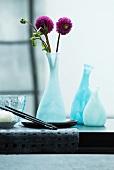 Moderne Blumenvase mit violetten Dahlien auf einem schwarzen Esstisch