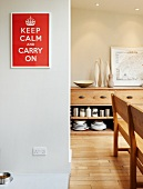 Red and white picture with slogan, sideboard and wooden bench in dining room