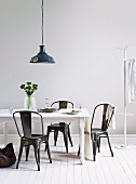 White lacquer, shabby chic dining table with black metal chairs and a black metal hanging lamp above