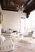 White, delicate wooden chair and floor cushions around small, white coffee table in elegant, Oriental loggia with dark, ornate wooden ceiling