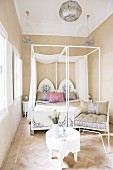 Oriental four-poster bed with painted headboard in bright, simple bedroom with mosaic stone floor and upholstered metal chair next to white side table