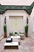 Oriental courtyard with white designer table on terracotta floor, geometric painting in niche, symmetrical sconces, vase-shaped planters and wooden panels painted dark green running around upper wall