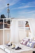 Invitingly arranged, modern daybed with gauzy fabric canopy on Oriental roof terrace below open, blue sky