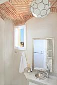 Kugelförmige Pendelleuchte an Gewölbedecke aus Ziegel über schlichtem Waschtisch mit Spiegel in orientalischem Bad; kleiner Ausblick durch das Fenster