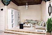 Loggia in orientalischem Stil mit Polstermöbeln und modernem Tischmöbel auf abgestuftem Podest; eine prachtvolle Holzdecke und eine silberfarbene verzierte Pendelleuchte lassen hohe Kunstfertigkeit erkennen