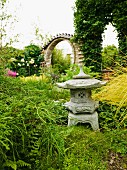 Toro lantern in established, ornamental Japanese garden with round, brick doorway in background and summery, meditative atmosphere