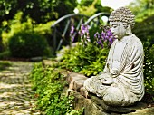Stone statue of seated Buddha on rough, low stone wall lends meditative atmosphere to ornamental garden with cobbled path leading to small bridge