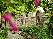 Blick auf kunsthandwerkliche Gartenmauer in Sichtmauerwerk mit kugelförmig geschnittenen Buxbüschen und gepflastertem Gartenweg davor
