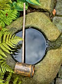 Water in round stone basin with chiselled channel and wooden ladle lying on top; ferns grow throughout the garden