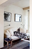 Elegant white sofa and antique, upholstered stool beneath two black and white photographs