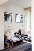 Elegantes Sofa in Weiss und Polsterhocker im Antikstil unter zwei Schwarzweiss-Fotografien