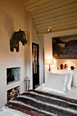 Metal horses head hanging on the wall of a cozy bedroom with a small fireplace a wood panel, pitched ceiling