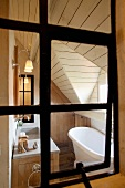View through an old iron window into the elegant yet cozy bathroom of a country home with a wood panel, pitched ceiling