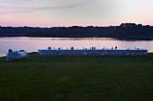 Lange Festtafel mit weissen Klappstühlen am Meer bei Sonnenuntergang