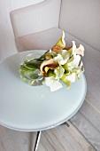 weiße und cremefarbene Calla-Blumen in einer Kugelvase auf einem Milchglastisch