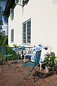 Teatime auf sonniger Terrasse mit neu gepolstertem Antiksofa und leichten, blauen Gartenmöbeln im Vintage-Look