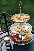 A tiered cake stand with dainty treats on a balcony table, with decorative railings in the background