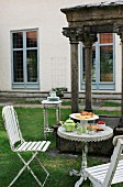 Afternoon tea in garden with antique bistro table and white vintage chairs in front of historical stone pavilion
