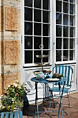 Vintage garden furniture made from blue-painted metal in front of terrace door of old house - afternoon tea with silver cake stand and blue china teapot