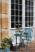 Vintage Gartenmöbel aus blau lackiertem Metall vor der Terrassentür eines alten Hauses - Teatime mit Silber-Etagere und blauer Porzellan-Teekanne