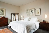 Double bed with white bed linen flanked by designer pendant lamps and next to dressing gowns hanging on screen