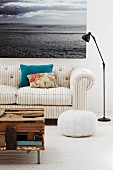 Coffee table made from flotsam, grey and white striped sofa and large seascape photograph on wall