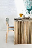 Wooden table made from many untreated wooden slats and grey chairs in front of white curtain