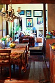 Kitchen dining room in country-house style with colourful pictures on living room wall in background