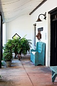 Entrance area of old country house with curved porch and antique bench painted light blue on large stone flags