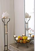 Wire candlestick used as fruit basket on wicker table and large mirror in corner of bright room