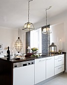Brightly lit kitchen counter below lamps with glass lampshades; elliptical pendant lamp above dining table