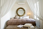 Stately bed behind open curtains; large, round, gilt-framed mirror above head