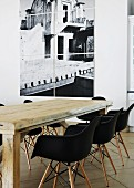 Rustic wooden table and black Eames shell chairs in front of multi-panel photograph on white wall