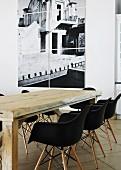 Rustikaler Holztisch mit schwarzen Eames Stühlen vor hängendem Fotobild an weisser Wand