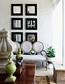 Group of square mirrors with black frames on white wall behind Baroque sofa with white upholstery