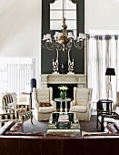 Black and white colour scheme and eclectic furnishings in traditional living room with open fireplace and large, brown leather couch