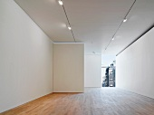 Empty gallery space lit by spotlights in the ceiling and wood flooring (Photographers' Gallery, London)