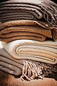 Gestapelte Wolldecken in verschiedenen Naturfarben