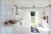 White designer kitchen with carpet runner in front of an open patio door and view of the garden
