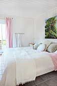 Double bed with white comforter in a white paneled bedroom