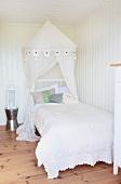 Bed with a canopy and white lace bedspread in a white paneled room