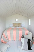 Bedroom with white wood paneling on the wall and ceiling in a little house